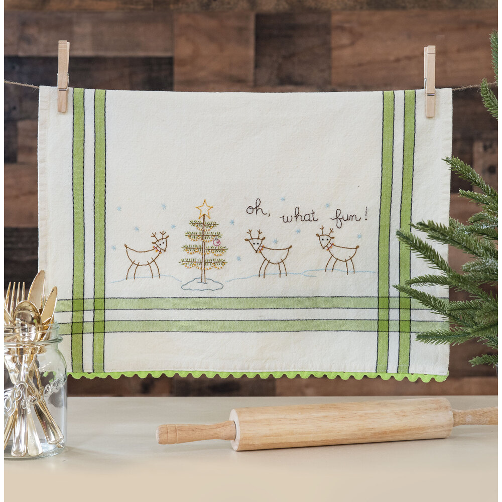 The adorable Oh What Fun Vintage Kitchen Towel hanging from clothespins