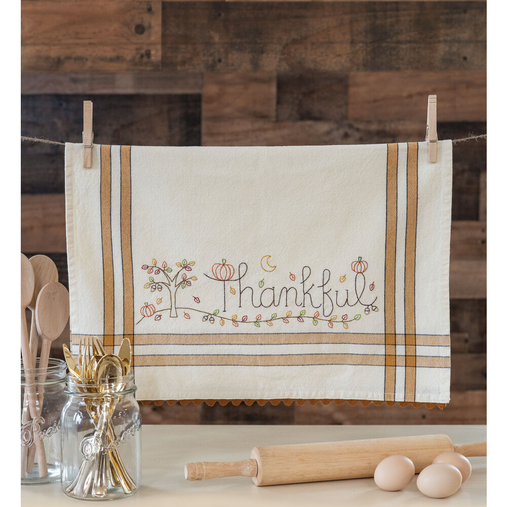 The adorable Thankful Vintage Kitchen Towel hanging from clothespins