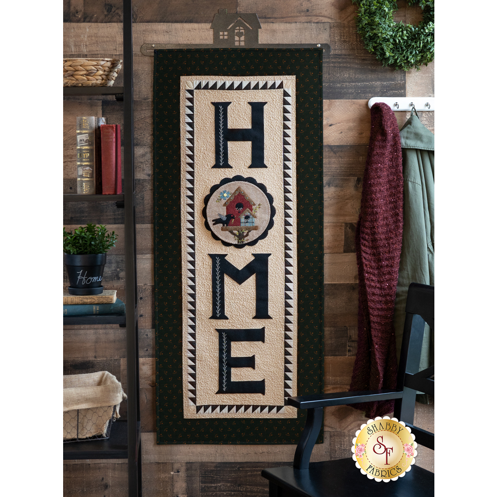 The Welcome Home Wool Applique Wall Hanging displayed on a wall - Shabby Fabrics