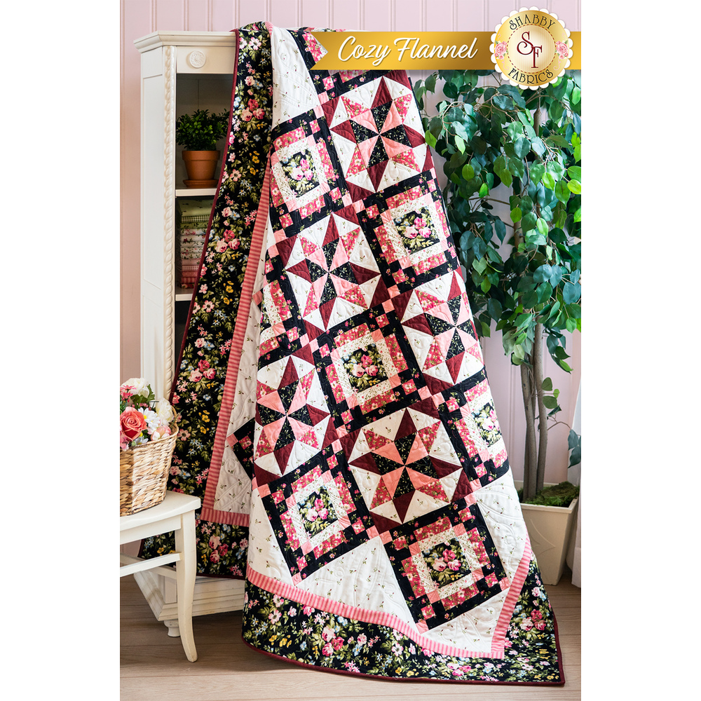 Pink and black floral themed flannel quilt draped over a bookcase