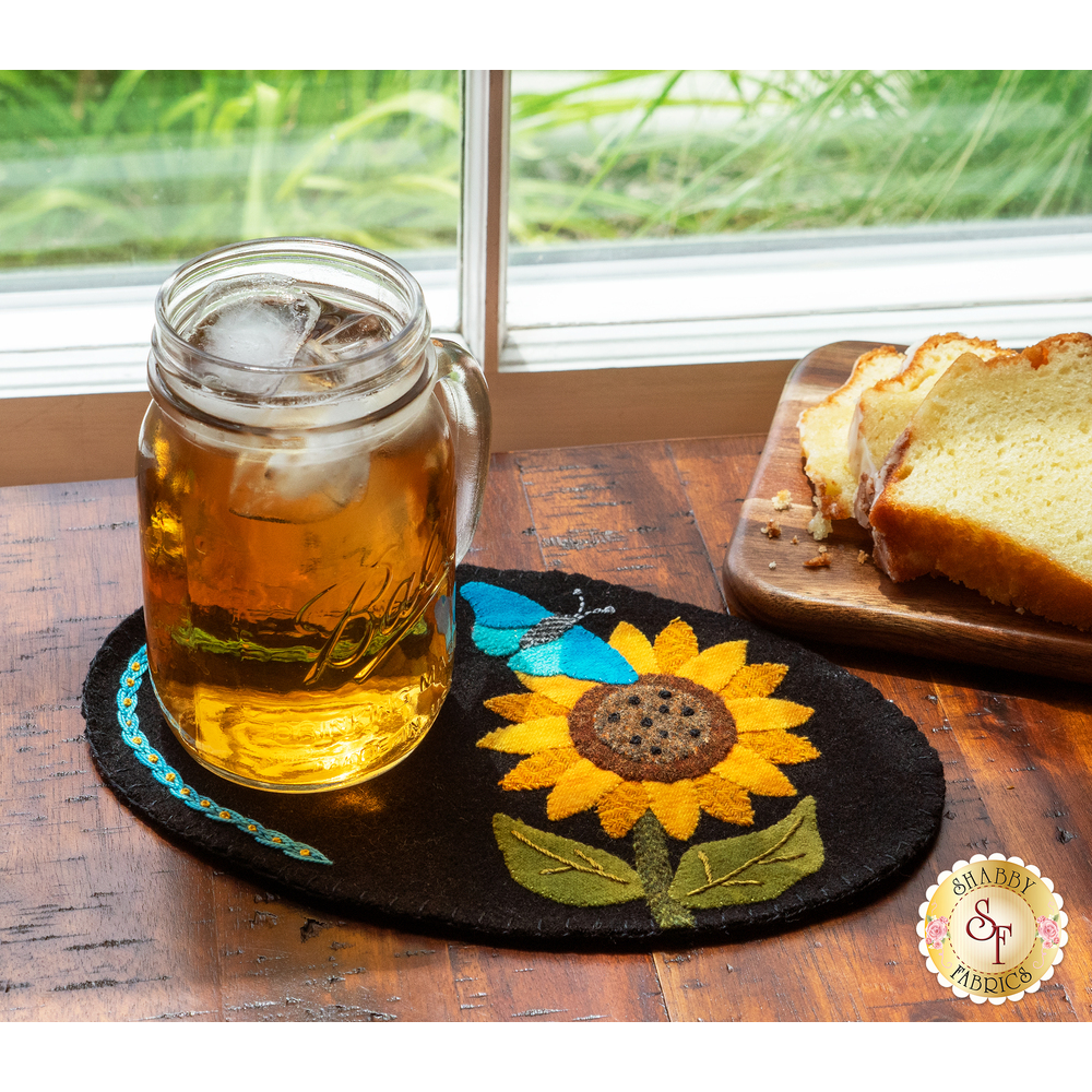 Black wool mug mat with a beautiful applique butterfly and sunflower and jar of sweet tea on top