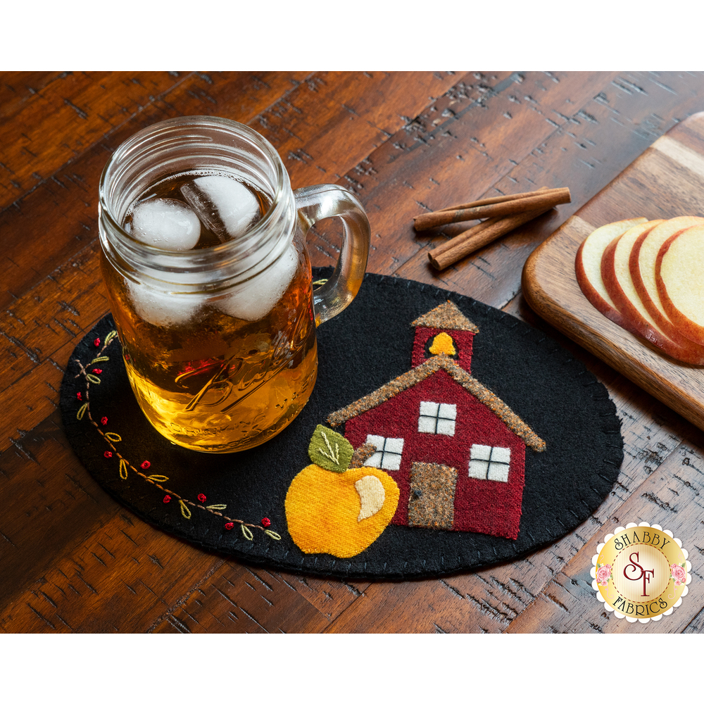 Small black wool mat with a school house and yellow apple stitched down, topped with a glass of tea