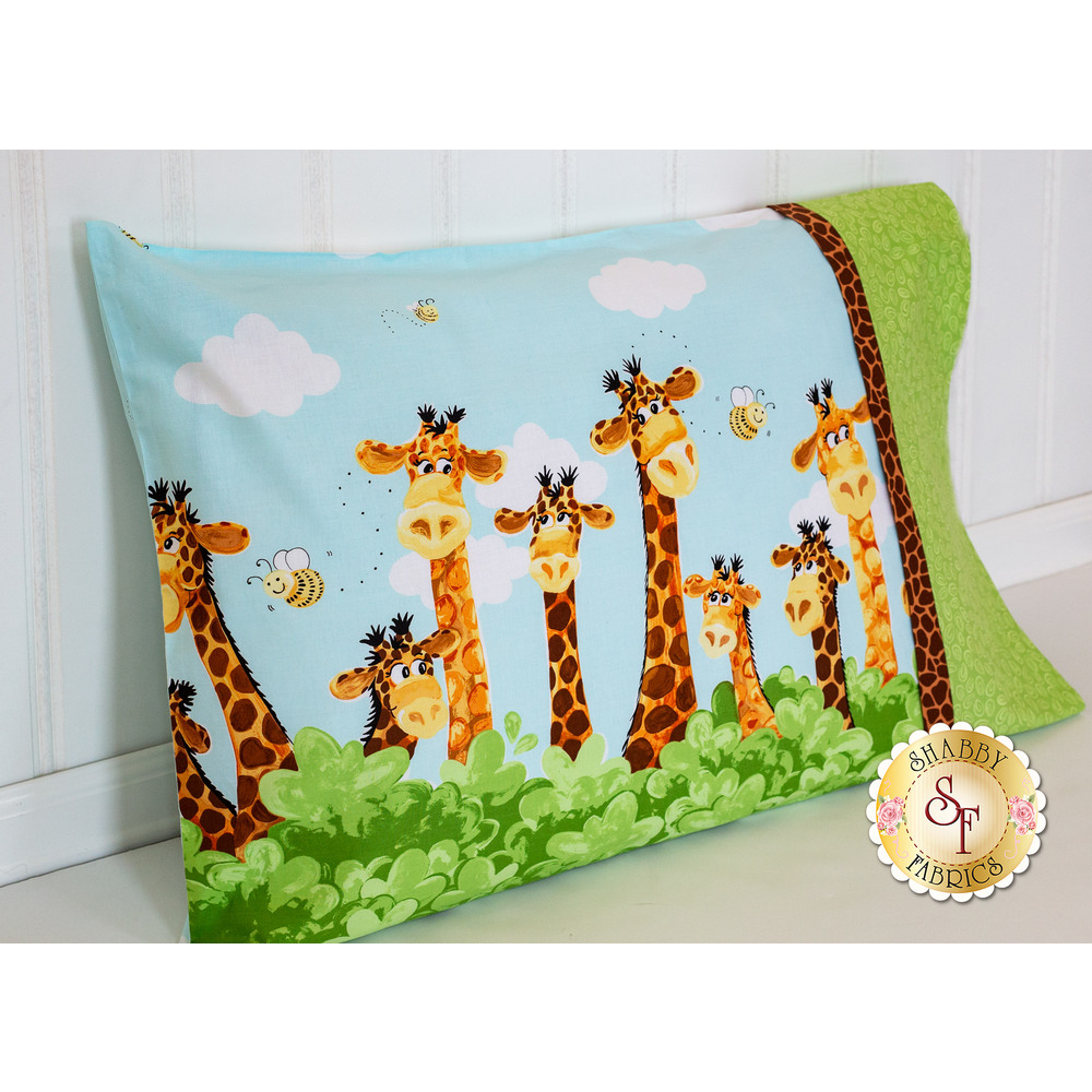 Pillowcase with adorable giraffes resting against a wall
