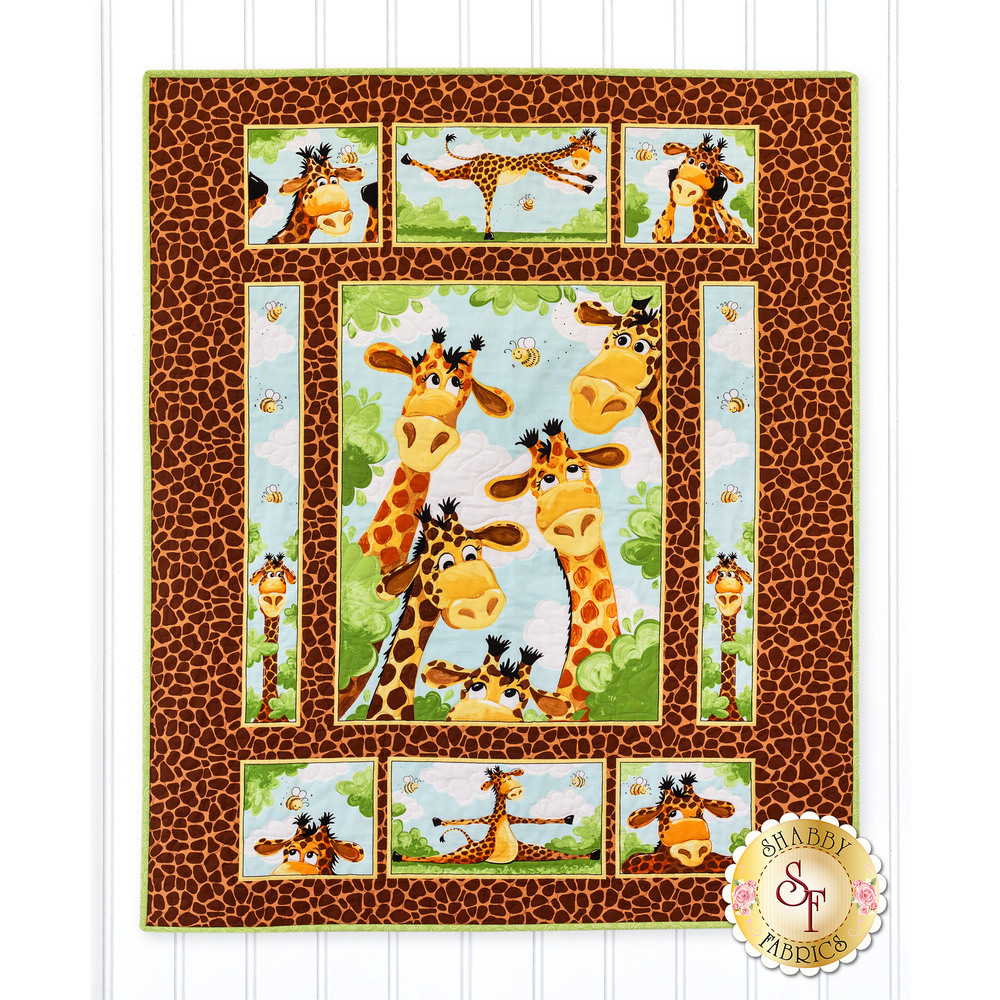 The adorable Zoe the Giraffe Panel Quilt hanging on a wall