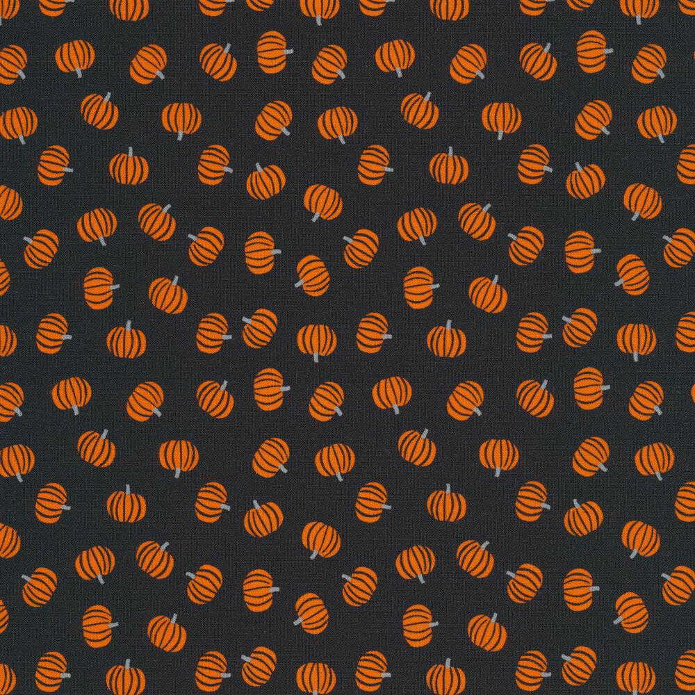 Tossed orange pumpkins on a black background