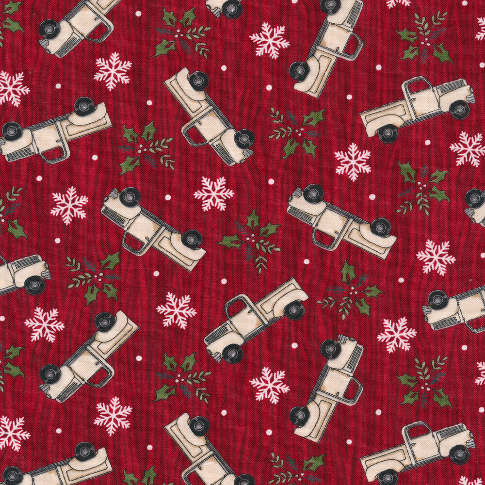 Tossed vintage trucks, snowflakes, and holly on a red wood grain background