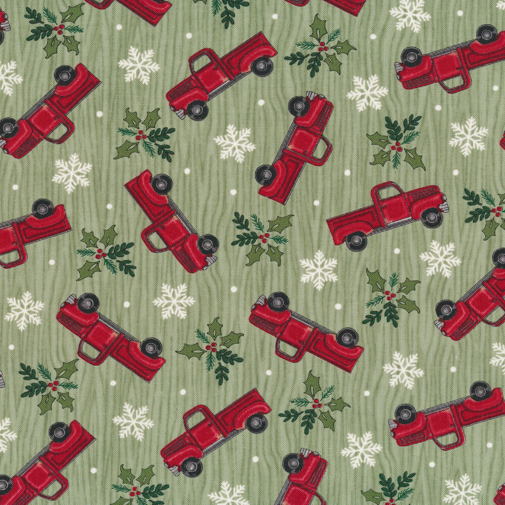 Tossed vintage trucks, snowflakes, and holly on a green wood grain background