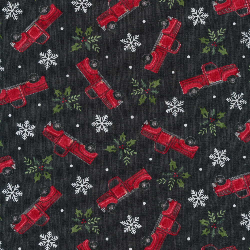Tossed vintage trucks, snowflakes, and holly on a black wood grain background