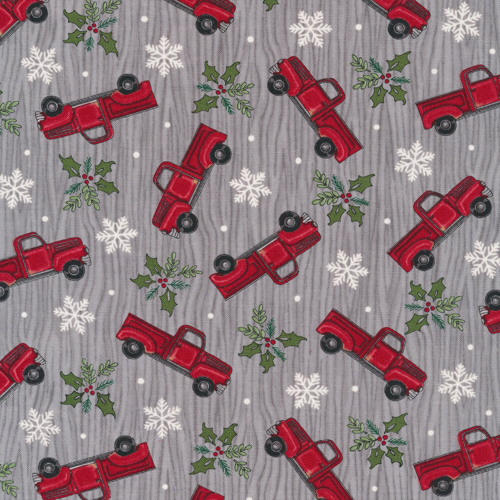 Tossed vintage trucks, snowflakes, and holly on a gray wood grain background