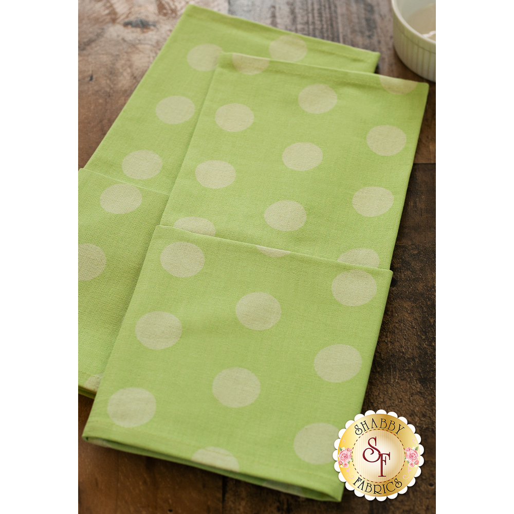 Light green towels with tonal polka dots displayed on table | Shabby Fabrics
