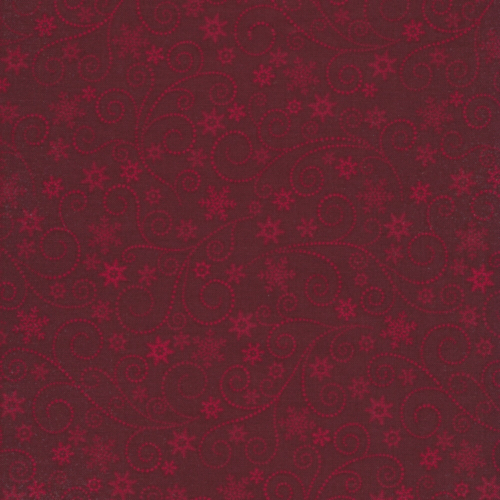 Red tonal fabric with dotted swirls, stars, and snowflakes