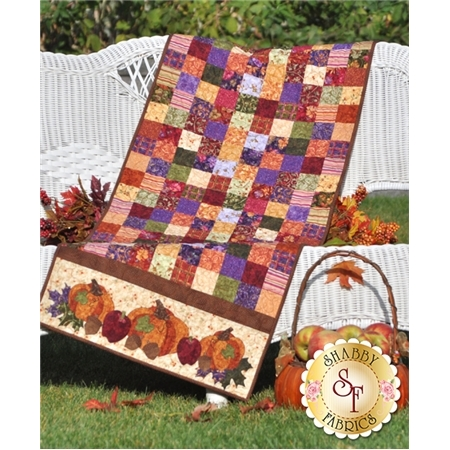 Table runner from purple, red, and orange patchwork squares with harvest pumpkin applique on ends.