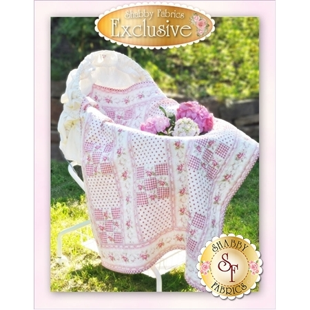 9-patch pink and white baby quilt with pink rose florals resting in bassinet.