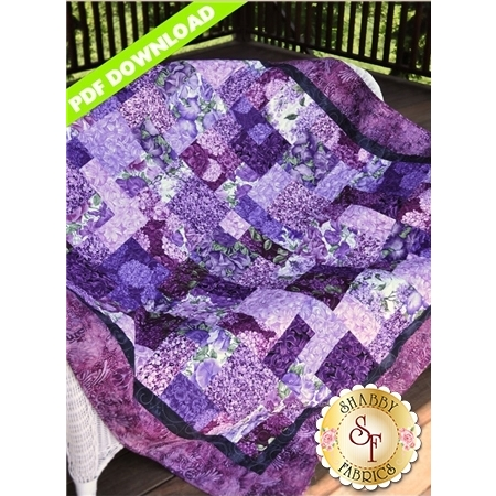 Simple pieced rectangles quilt featuring purple floral fabric collection.