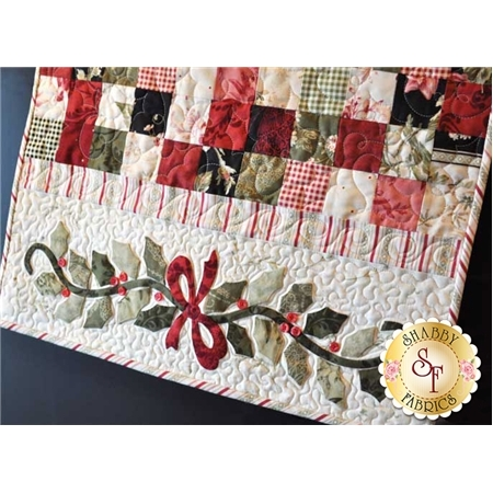 Red, green, and cream patchwork table runner with holly applique and bow.