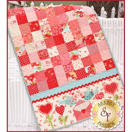 Pink patchwork table runner made from simple squares with kissing lovebirds applique.
