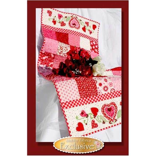 Table runner made of red, pink, and white patchwork squares and heart appliques.