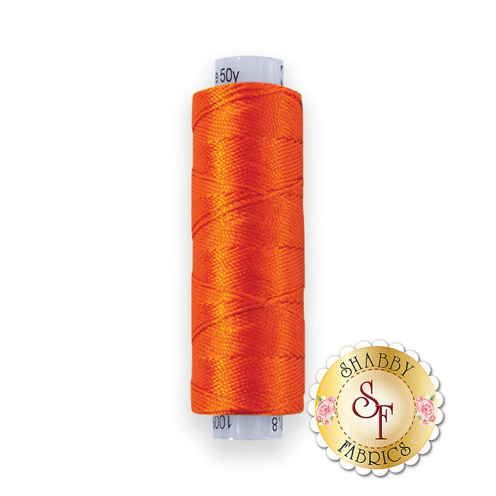 Orange thread on a spool | Shabby Fabrics