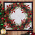 A white square table topper with a green and red wreath pieced design hanging on a wall