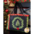 Christmas tote with black handles, cream fabric with Christmas trees, and red bows