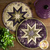 The coordinating cream and purple Clover Meadow Hot Pads on a wood table